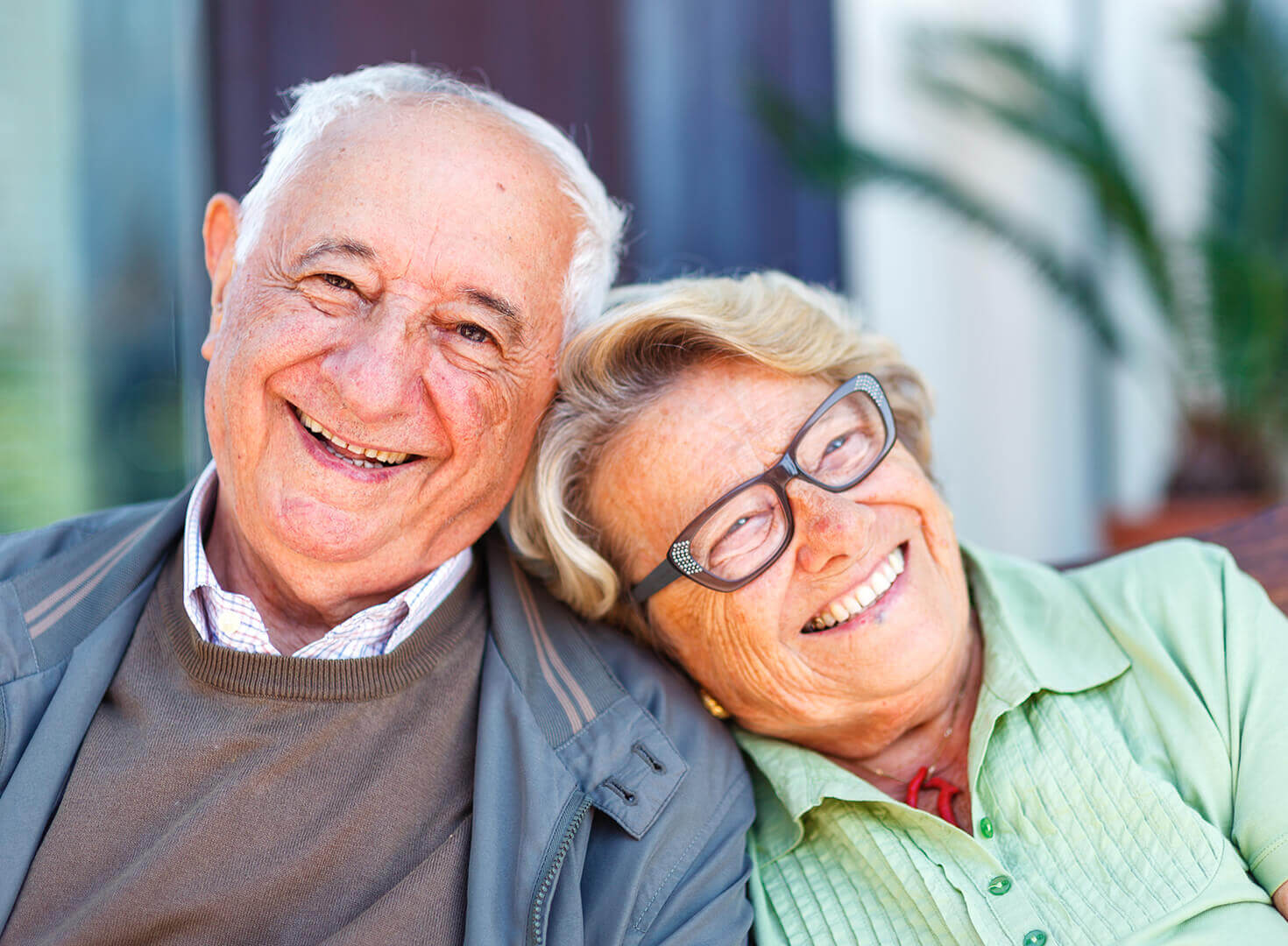 Senior couple smiling, leaning heads against one another happy