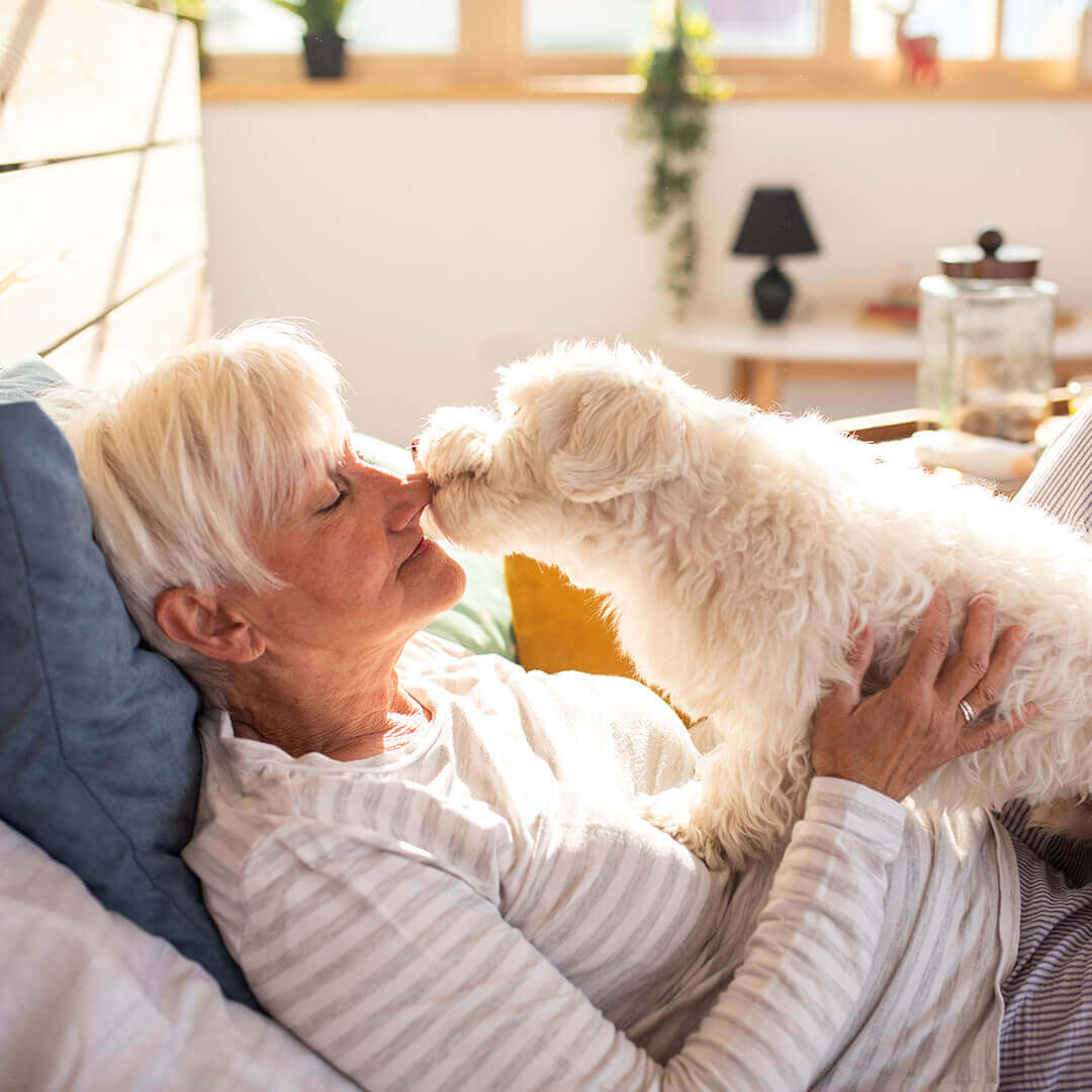 Senior woman laying in bed with dog licking her face