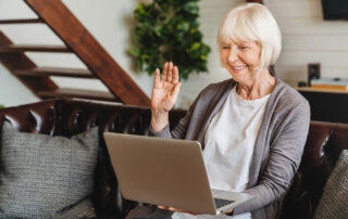 Senior woman sitting on couch on video chat with family