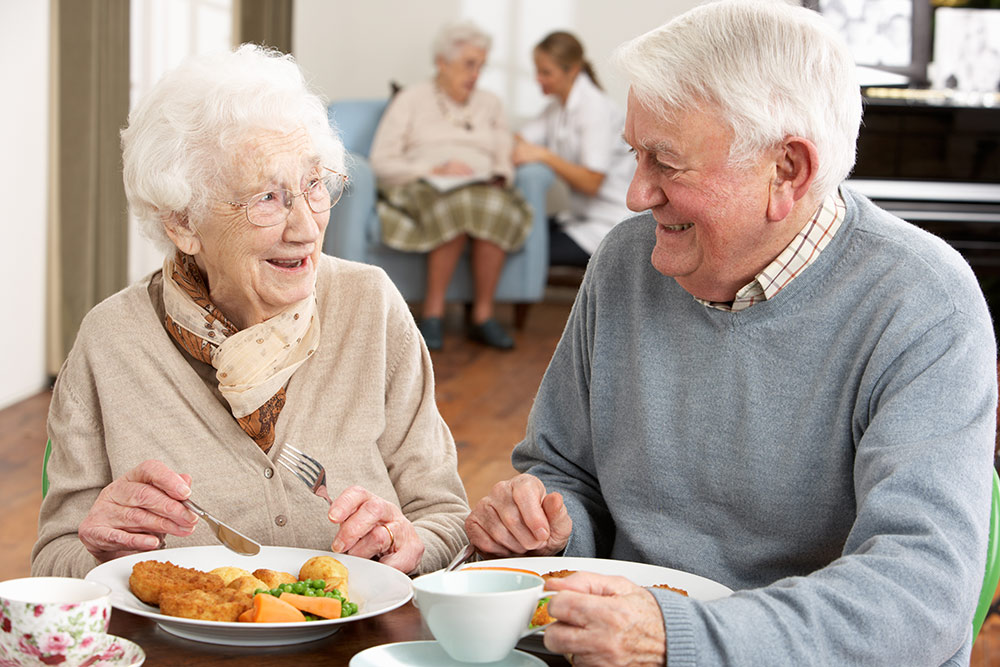 Senior couple smiling and eating lunch in senior living community