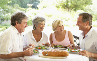 Group of senior friends eating lunch outside, talking and smiling