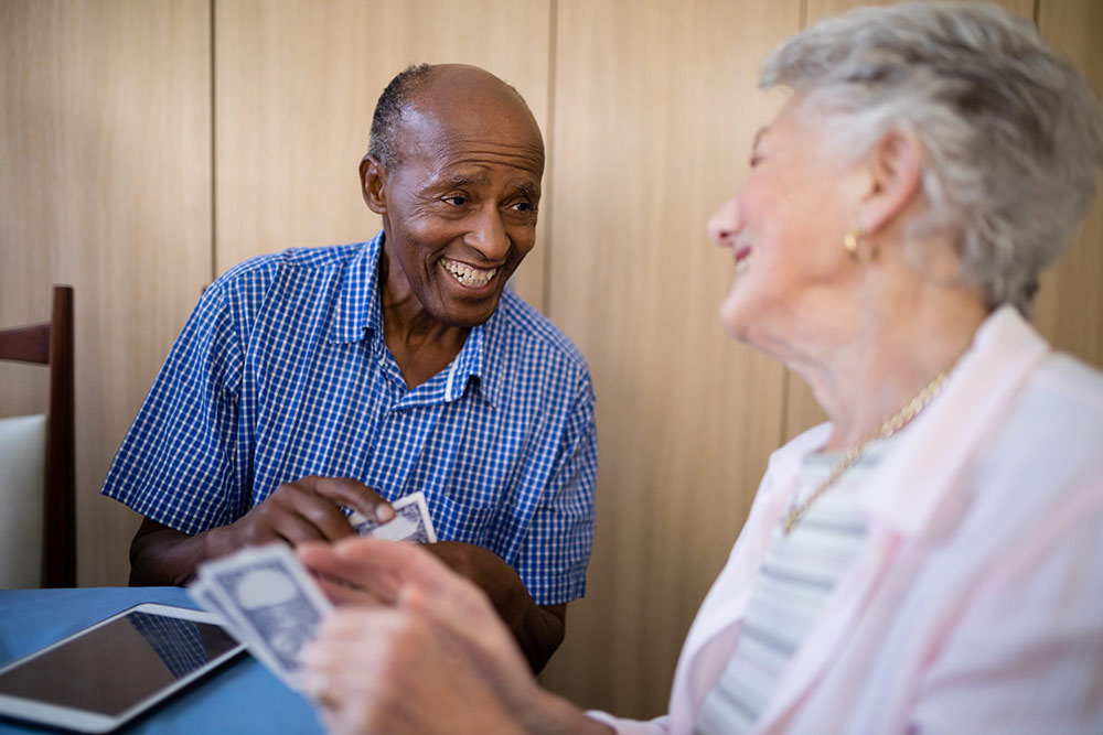 Senior man and woman sitting at table smiling and playing cards in senior living community