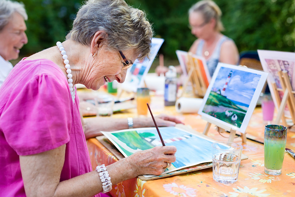 Residents in senior living community painting together outside, arts and crafts