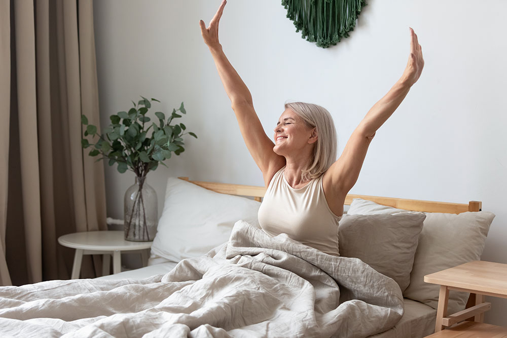 Senior woman sitting up in bed with arms stretched up and smiling, rested and ready for the day
