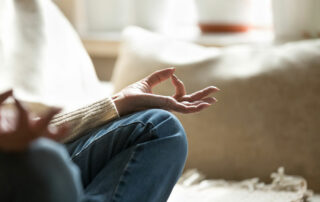 Close up of senior woman's hands, sitting on couch, meditating