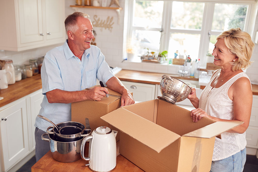 Senior man and woman packing up kitchen items into boxes