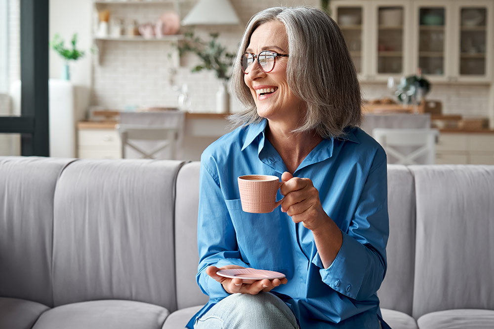 Happy senior woman sitting on couch in living room drinking coffee