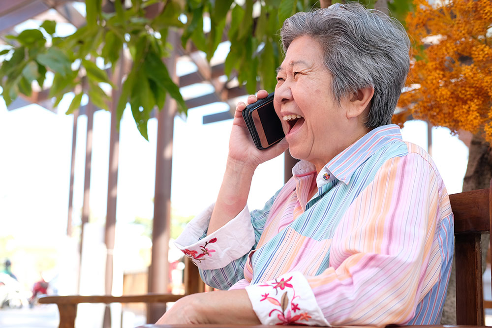 Happy senior woman sitting outside talking on phone and laughing